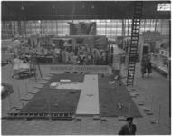 182-4 Een enorme maquette van vliegveld Zestienhoven op de vloer van een hal.