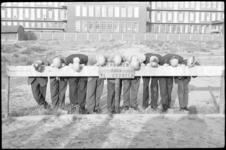 1833 Kaalgeschoren studenten hangen over een hek met het bord 'Verboden vuil te storten'.