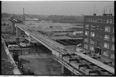20991-1-27 Tramviaduct Schieweg in aanbouw. In het midden de kruising met de Gordelweg en het Noorderkanaal.