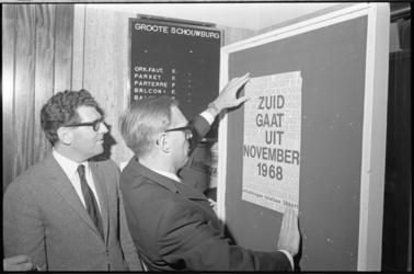 21006-1-22 Op de persconferentie in de Groote Schouwburg aan het Zuidplein hangt wethouder J. Reehorst het eerste ...