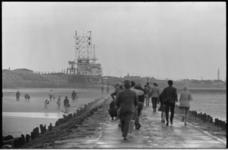 21058-2-15 Dagjesmensen wandelen op het strand en op het Noorderhoofd in een winderig Hoek van Holland. Op de ...