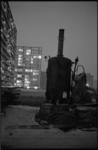 21092-3-31 Avondimpressie van de wijk Ommoord in aanbouw met het donkere silhouet van een oude stoomheimachine.