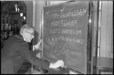 21225-1-2 Burgemeester W. Thomassen schrijft met krijt op een bord dat mevrouw Thomassen griep heeft maar iedere ...