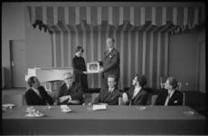 21271-4-23 De muziekcriticus G.M. Dersjant (rechts) reikt in het Hilton hotel de eerste exemplaren van een ...