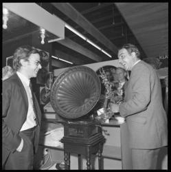 22071-4-6 Willem Duys (rechts) plaatst de naald op een ouderwetse grammofoonplaat-installatie; Disk-directeur Lou Thiel ...