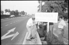 22102-5L Bewoners plaatsen een door henzelf gemaakt verkeersbord ('Afremmen') op de Hoofdweg.