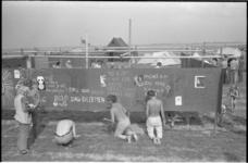 22123-5 Jeugd beschildert een wand met aan het milieu gerelateerde teksten tijdens een protestcamping, gericht tegen ...
