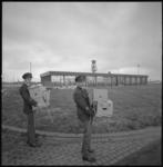 22319-5 Twee douane-beambten poseren met verhuisdozen; op de achtergrond het nieuwe gebouw voor vier rijksdiensten, en ...