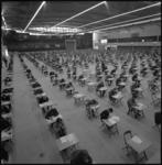 22401-3-8 Groot overzicht in Ahoy'-complex (Zuiderpark) met studenten aan tafeltjes tijdens examens.