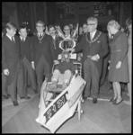 22409-4-12 Echtpaar Thomassen en studenten van het Rotterdamse Studenten Corps bij een kinderwagenachtig vervoermiddel ...