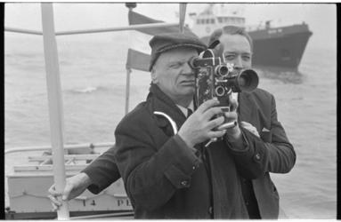 22429-5-18 Filmer- en fotograaf J. van Rhijn filmt de berging van het in Dordrecht gezonken rijnschip 'Rotterdam'.