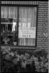 22720-7-26 Een met de hand geschreven raambiljet op een raam van een woonhuis 'voor behoud van vliegveld Zestienhoven'.