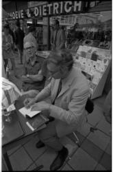 22754-1-19A Godfried Bomans signeert zijn boek Pieter Bas voor de boekwinkel van Voorhoeve en Dietrich aan de Lijnbaan.