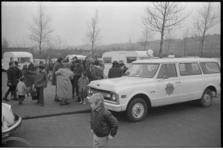 22952-3-30 Politie begeleidt Italiaanse zigeuners de stad uit. Op de voorgrond een Chevrolet C-10 patrouillewagen. Zij ...
