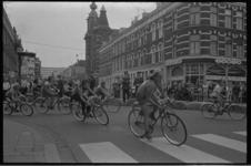 23619-1-10A Wielrenners rijden vanuit de Noordmolenstraat rechtsaf de Jacob Catsstraat in. Op de achtergrond de Noorderkerk.