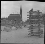 23670-1-7 Jeugd op houten klimrekken in het gebied Goudseplein - Goudse Rijweg. Op de achtergrond de RK-kerk aan de ...