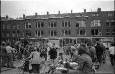 23710-7-10 Belangstellend publiek in de Wapenstraat tijdens het herstellen van de ingegooide ramen.