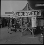 23735-2-11 Een kraam en spandoek 'Vredesweek ' in winkelcentrum Hesseplaats.