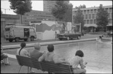 23737-6-10 Mensen op een bankje kijken naar het beschilderen van een dienstgebouwtje op het Schouwburgplein.
