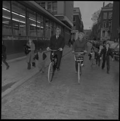 23928-1-11 Zuster M.P.C. Haaijer en burgemeester W. Thomassen fietsen in de Eendrachtsstraat.