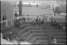 23947-3-32 Publiek zit op de trappen van het 'openluchttheater' het Kuipje in winkelcentrum Zuidplein.