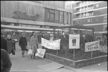 23954-2-30 Winkelend publiek kijkt ter hoogte van schoenenzaak Huf naar de in een plantenbak gestoken protestborden en ...