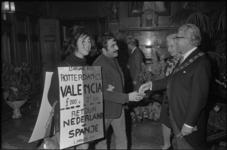 23956-2-39 Nel Soetens (links), behangen met sandwichborden van comité Pro Gastarbeiders, tijdens de nieuwjaarsreceptie ...