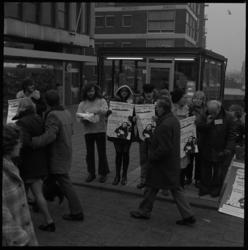 23984-4-1 Mensen met tekstborden tegen de oorlog in Vietnam bij de ingang van het Amerikaanse consulaat aan de Vlasmarkt.