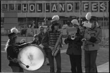 24321-2-26 Leden van een muziekkorps blazen op hun instrumenten, met de 'Holland-Festival-tekst'-gevel van de Doelen in ...