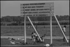 24337-6-83 Met een waarschuwingsbord worden de zonnebadende mensen gewezen op de risico's van het zwemmen in de ...