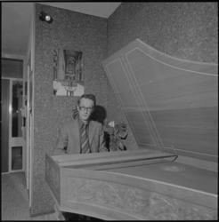 25144-1-3 Organist en koordirigent Aad van der Hoeven achter een klavecimbel. Op de achtergrond een interieurfoto van ...