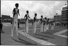 25278-4-14 Een dansgroep op stelten en gekleed in soldatenuniformen treedt op op het Schouwburgplein.
