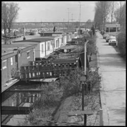 25833-4-4 Woonschepen langs het Noorderkanaal. Op de achtergrond het Kleinpolderplein. Er wordt gediscussieerd over een ...