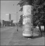25912-1-2 Een reclamezuil op de hoek van de Heer Bokelweg en de Noordsingel. Links de H.H. Antonius en Rosalia kerk ...
