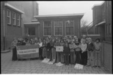 25998-3-15 Klas Eben Häezerschool toont exemplaren van dagblad Trouw.