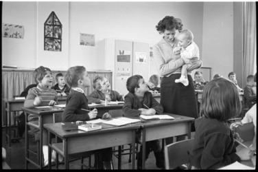 304666-7 Lerares met baby in een klas van de lagere school.