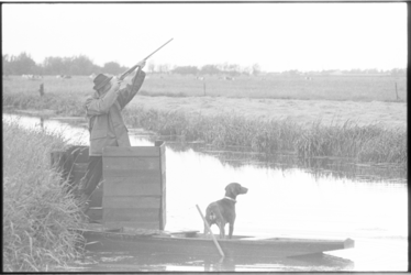 304843-4 Op vogels schietende jager met zijn hond in een polder bij Moordrecht.