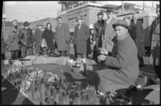 3050-2 Standwerker op de markt aan de Blaak zonder kraam heeft zijn waren uitgestald op trottoir en trekt veel publiek.