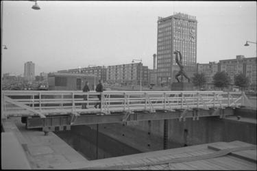 305943-26 Voetgangersbrug over de ingang van de Leuvesluis. Links het sluiswachtershuis naast Plein 1940 met het beeld ...