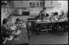 3070-3 Overzicht leslokaal B.L.O.school met meisjes en keukeninrichting.