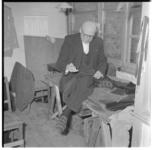 3094 De 76-jarige kleermaker G.J. Gerbscheid zit schrijlings op een tafel en is druk met draad en textiel.