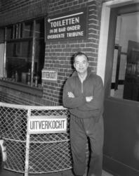 3146-2 Voetbaltrainer Denis Neville staat buiten bij een bord met de tekst 'Uitverkocht'.