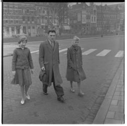 3153 Rosita en Elke, twee Duitse meisjes uit Osnabruck, lopen met een rechercheur van de Vreemdelingendienst, op straat.