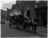 3246 Leerlingen van de Vakschool voor Bakkerij- en Hotelpersoneel zwaaien in de Rauwenhoffstraat vanaf een koets met paarden.