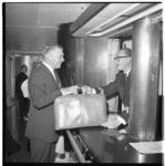 3284-1 Filmster Clark Gable (links) neemt bij een balie bagage in ontvangst op ss. Nieuw Amsterdam.