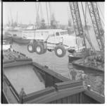 3304-1 Een kipkar hangt hoog boven het laadruim van een binnenvaartschip.