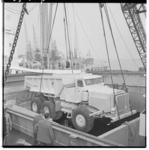 3304-2 Een kipkar hangt hoog boven het laadruim van een binnenvaartschip.