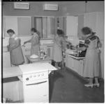 3313-1 Huisvrouwen aan het koken in de zuivelkeuken in het Bouwcentrum.