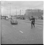 3316-2 Hoofdagent J. Kweekel gebiedt een automobilist op het Weena aan de kant te gaan.