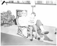 3321 Radioprogrammamaker en musicus Geert Elfferich met kind in rotanstoel.